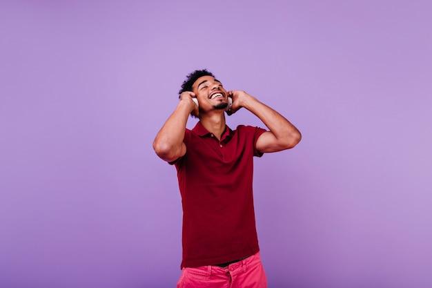 Szczęśliwy model mężczyzna słuchanie muzyki z zamkniętymi oczami. kryty strzał śmiejącego się beztroskiego mężczyzny w czerwonej koszulce pozowanie w słuchawkach.