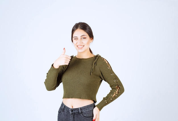 Szczęśliwy model młoda kobieta mrugając i pokazując kciuk do góry