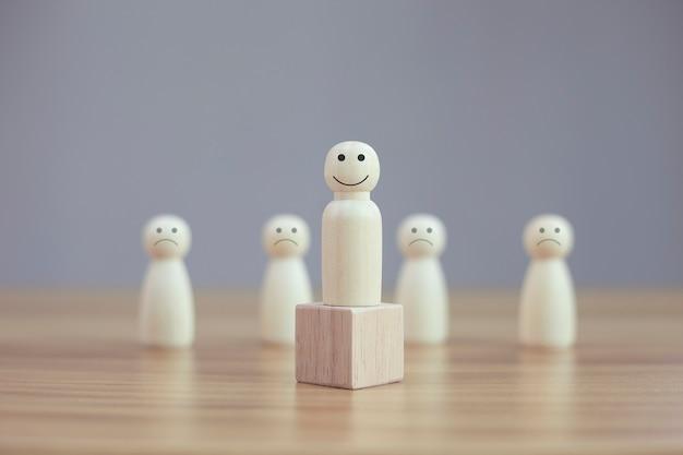 Szczęśliwy model osoby z drewna buźkę wśród niewyraźnej ikony smutnej twarzy ludzi na drewnianym stole