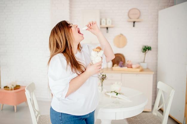 Szczęśliwy model plus size w dżinsach i białej koszulce, trzymający w dłoniach słodycz, otwierający usta w stylowej, jasnej kuchni. młoda pulchna kobieta w stroju casual. ciało jest pozytywne. conce