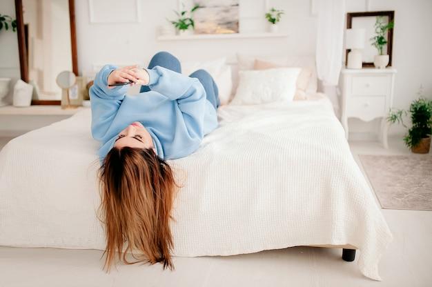 Szczęśliwy model plus size w dżinsach i niebieskim rowerze, trzymając telefon w dłoniach, leży na łóżku i patrzy na telefon. ciało jest pozytywne.