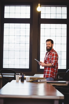 Szczęśliwy modniś używa pastylka komputer przy biurkiem