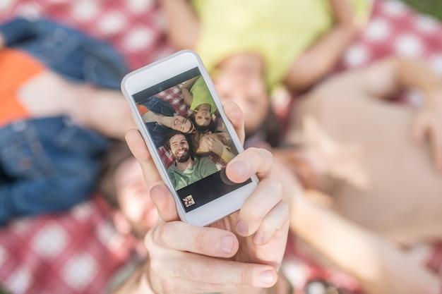 Szczęśliwy moment. ręka wyciągnięta od dołu do góry pokazująca zdjęcie odpoczywających radosnych młodych ludzi na ekranie smartfona