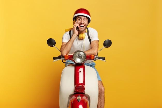 Szczęśliwy motocyklista pozuje na szybkim własnym transporcie, dzwoni do klienta przez smartfona, podróżuje na duże odległości, nosi kask, słuchawki stereo na szyi, uśmiecha się do kamery. mężczyzna kierowca prowadzi skuter