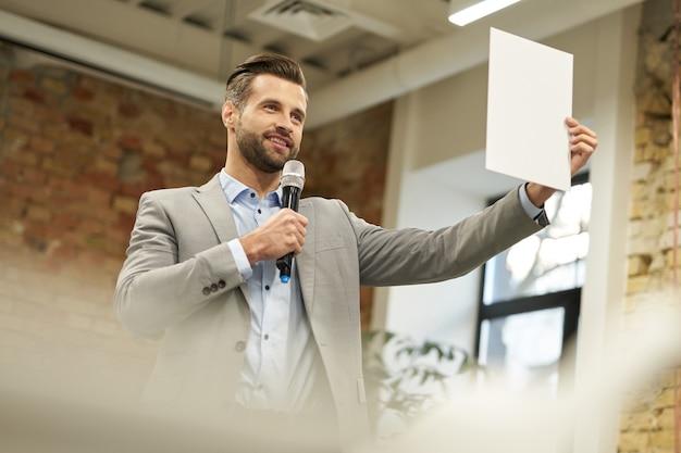 Szczęśliwy mówca demonstrujący coś na papierze