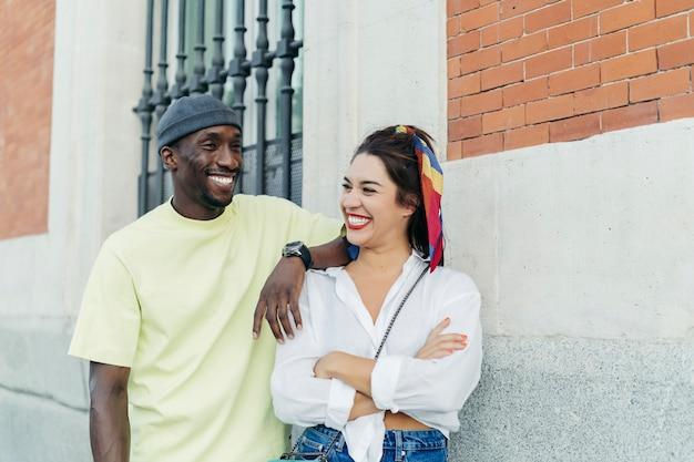 Szczęśliwy murzyn i kaukaski kobieta, patrząc na siebie. ona ma skrzyżowane ramiona, a on opiera się na dziewczynie. noszenie zwykłych ubrań. ściana na tle