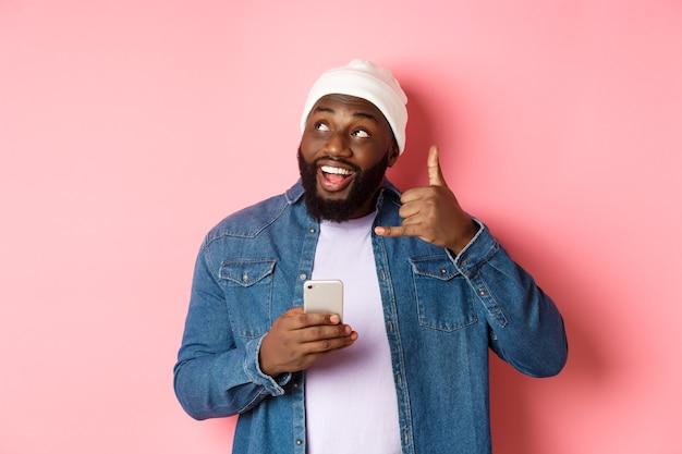 Szczęśliwy murzyn pokazując znak zadzwoń do mnie, wykonując gest telefonu i uśmiechając się, trzymając smartfon, stojąc w czapce i dżinsowej koszuli na różowym tle.