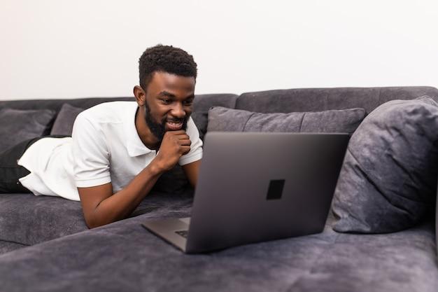 Szczęśliwy murzyn siedzi w domu sofa kanapa pracy lub korzystających z filmu internetowego w komputerze przenośnym w salonie