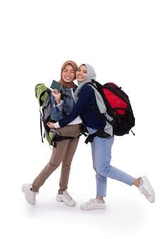 Szczęśliwy muzułmański backpacker ono uśmiecha się odizolowywam nad białym tłem