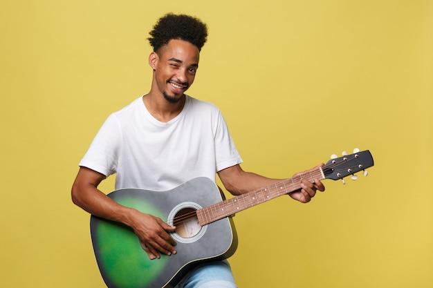 Szczęśliwy muzyk afroamerykanów mężczyzna pozowanie z gitarą