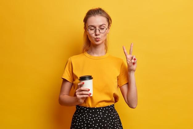 Szczęśliwy nastolatek bawi się w domu, ma złożone usta, zamknięte oczy, wykonuje gest pokoju, lubi pić kawę na wynos, nosi jasnożółtą koszulkę, okulary optyczne, pozuje w domu