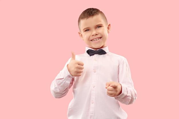 Szczęśliwy nastolatek chłopiec uśmiecha się na białym tle na różowym studio