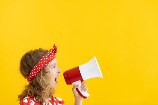 Szczęśliwy nastolatek dziewczyna trzyma czerwony głośnik przed żółtą ścianą