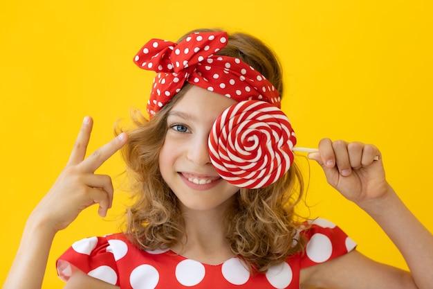 Szczęśliwy nastolatek dziewczyna trzyma czerwony lizak przed żółtą ścianą