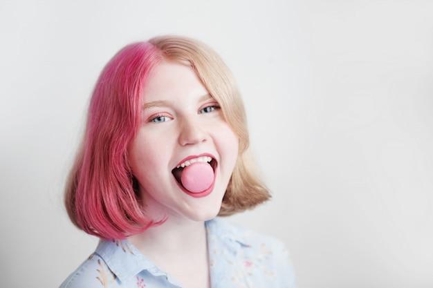 Szczęśliwy nastolatek dziewczyna z różowymi włosami z makaronikiem