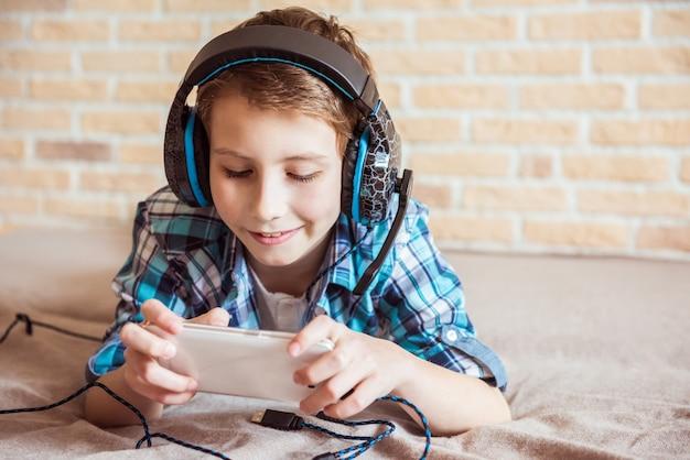 Szczęśliwy nastolatek grając w smartfonie z podłączonym zestawem słuchawkowym