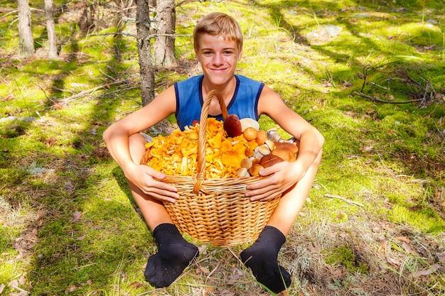 Szczęśliwy nastolatek siedzi w jesiennym lesie z dużym koszem kurek i borowików