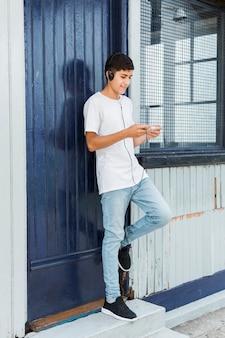Szczęśliwy nastoletni chłopak stoi przy zamkniętym błękitnym drzwi używać telefon komórkowego z hełmofonem na jego głowie