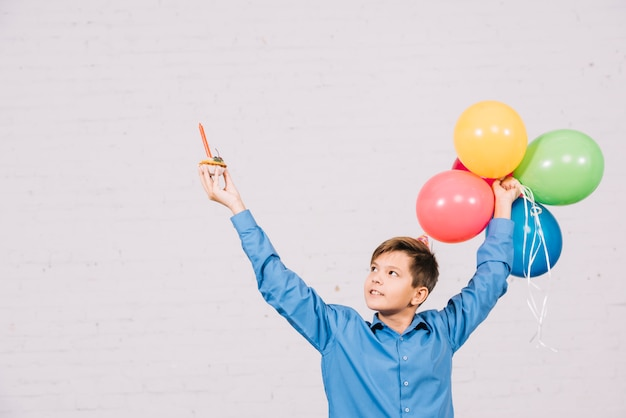 Szczęśliwy nastoletniego chłopaka mienia słodka bułeczka i kolorowi balony podnosi jego rękę