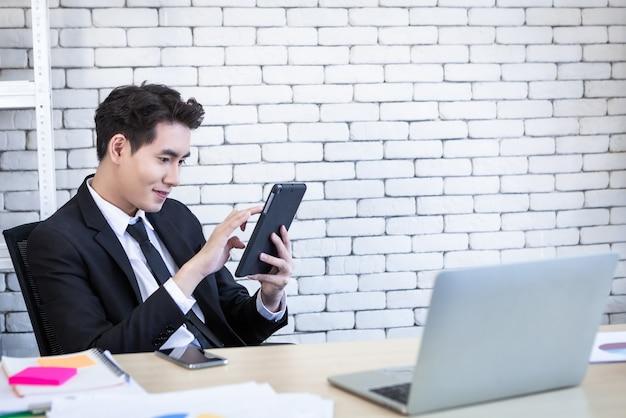 Szczęśliwy nastrój wesoły udany azjatycki młody biznesmen pracujący ze stołem i laptopem na drewnianym stole w tle w biurze