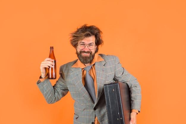 Szczęśliwy nauczyciel pije butelkę alkoholu po ciężkim dniu trzymając walizkę w ręku sekretarz