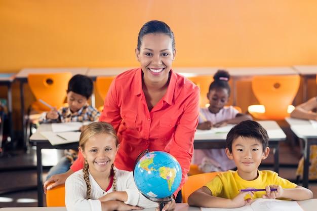Szczęśliwy nauczyciel pozuje z dwa uczniami