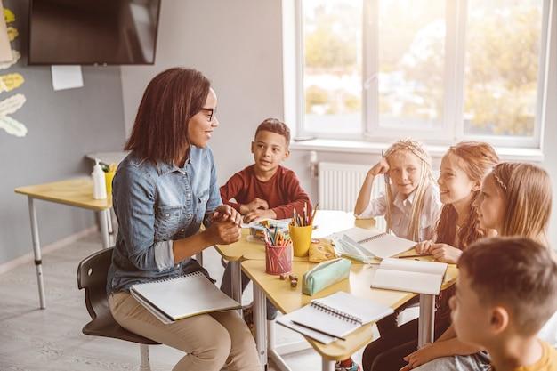 Szczęśliwy nauczyciel prowadzący lekcję z dziećmi w klasie