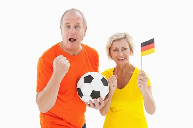 Szczęśliwy niemiecki para doping przy kamery mienia piłką