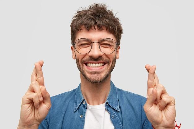 Szczęśliwy, nieogolony mężczyzna z szerokim uśmiechem, pokazuje białe zęby, krzyżuje palce na szczęście, będąc w dobrym nastroju stoi nad białą ścianą w modnej dżinsowej koszuli. pozytywny facet robi gest nadziei