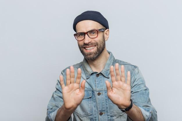 Szczęśliwy, nieogolony młody mężczyzna o atrakcyjnym wyglądzie pokazuje dłonie, jak coś zaprzecza lub demonstruje swoją odmowę