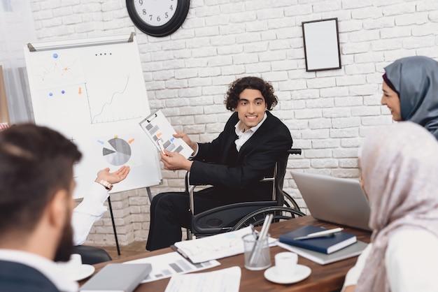 Szczęśliwy niepełnosprawny mężczyzna robi prezentację w biurze
