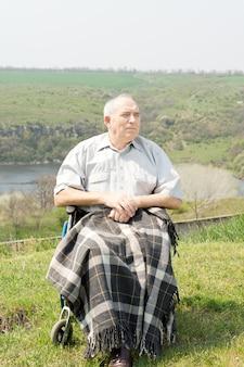 Szczęśliwy niepełnosprawny starszy mężczyzna ciesząc się słońcem siedząc na wzgórzu z malowniczym widokiem z kocem na nogach