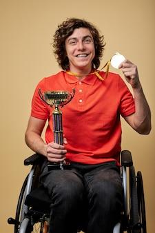 Szczęśliwy niepełnosprawnych paraolimpijskich sportowca na wózku inwalidzkim, trzymając mistrz puchar i złote medale na białym tle na beżowym tle