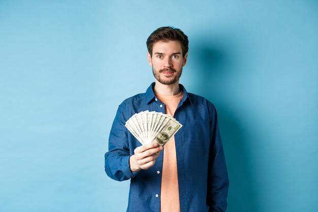 Szczęśliwy nowoczesny facet trzyma pieniądze i uśmiechnięty, stojąc na niebieskim tle.