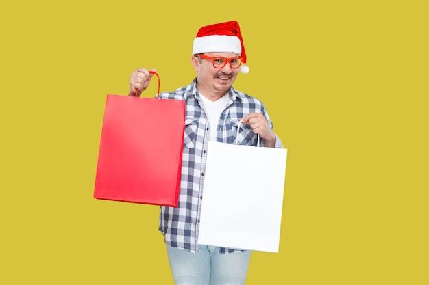 Szczęśliwy nowoczesny mężczyzna w średnim wieku w stylu casual i czerwony nowy rok czapka mikołaja, okulary i koszula, trzymając pakiety na zakupy z uśmiechem zębów, patrząc na kamery. kryty, odizolowany na żółtym tle