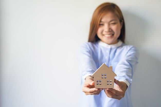 Szczęśliwy nowy właściciel domu trzymając model domu w dłoniach