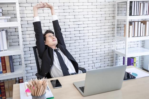Szczęśliwy odcinek się udanego azjatyckiego młodego biznesmena na laptopie, smartfonie i ołówku na notebooku w tle pokoju biurowego.