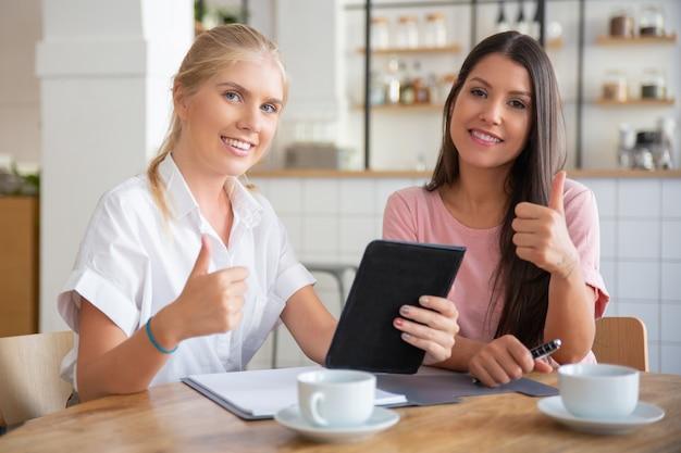 Szczęśliwy, odnoszący sukcesy agent i zadowolony klient, pokazując kciuk w górę, siedząc przy stole i razem używając tabletu