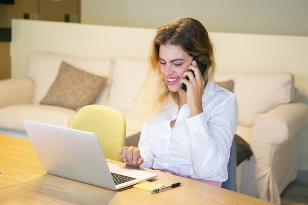 Szczęśliwy, odnoszący sukcesy menedżer omawiający projekt z klientem przez telefon