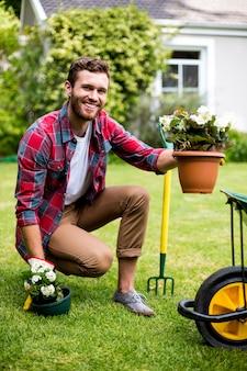 Szczęśliwy ogrodnika mienie puszkować rośliny w jardzie