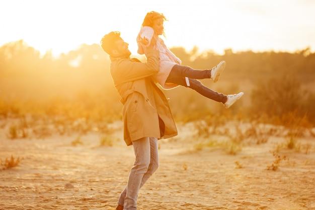 Szczęśliwy ojciec bawić się z jego małą córką przy plażą
