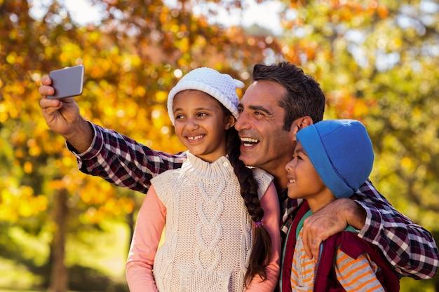 Szczęśliwy ojciec bierze selfie z dziećmi przy parkiem