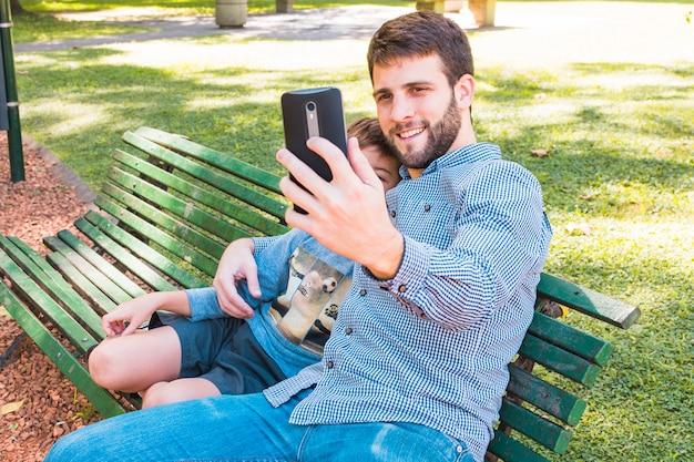 Szczęśliwy ojciec bierze selfie z jego synem na telefonie komórkowym w parku