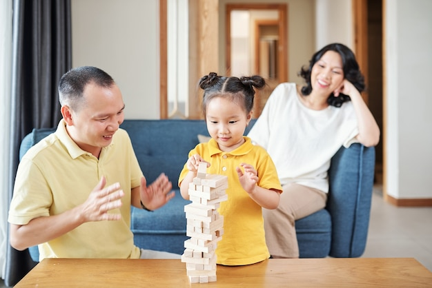 Szczęśliwy ojciec brawo dla ślicznej małej wietnamskiej dziewczynki budującej wieżę z drewnianych klocków