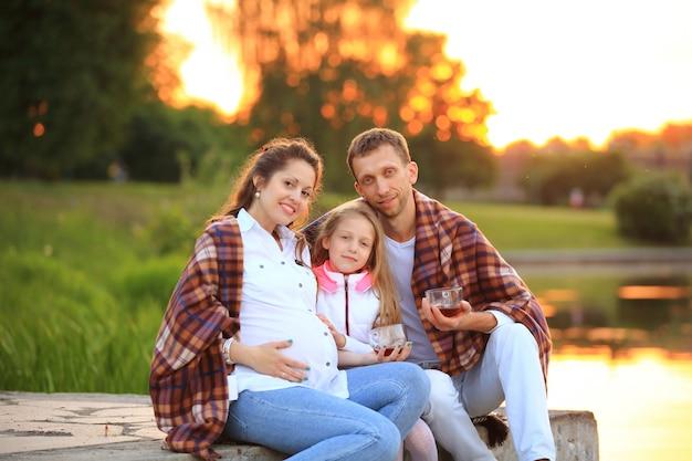 Szczęśliwy ojciec córki i ciężarnej mamy na pikniku