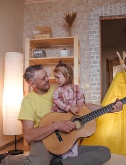 Szczęśliwy ojciec gra na gitarze dla swojej córeczki. opieka i edukacja dzieci