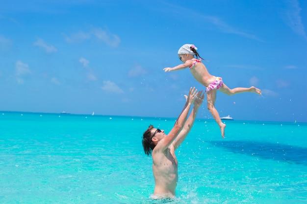 Szczęśliwy ojciec grać z małą córeczką w idealnym morzu