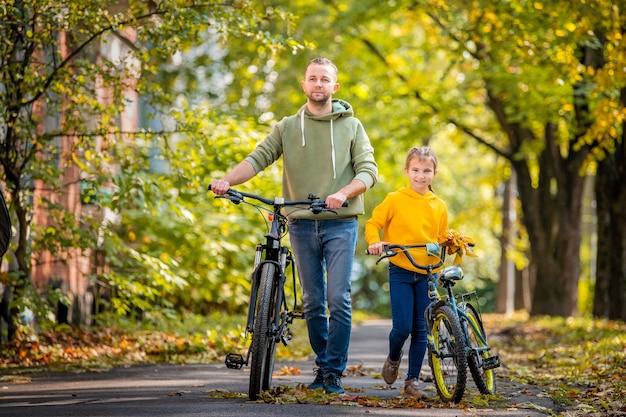 Szczęśliwy ojciec i córka chodzą z rowerami w jesiennym parku w słoneczny dzień.