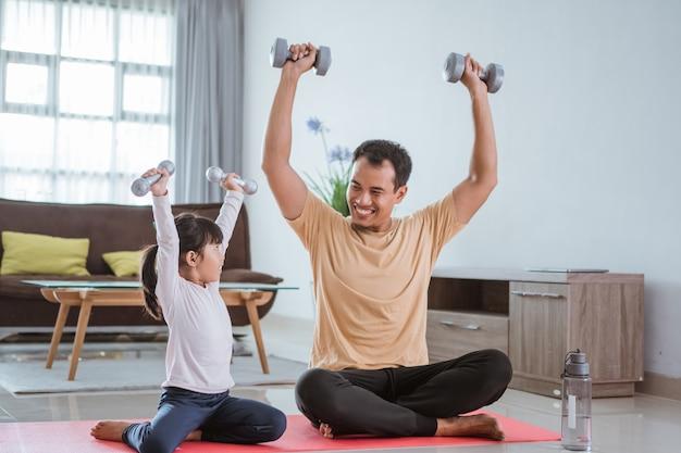 Szczęśliwy ojciec i córka ćwiczenia razem podnosić hantle w salonie