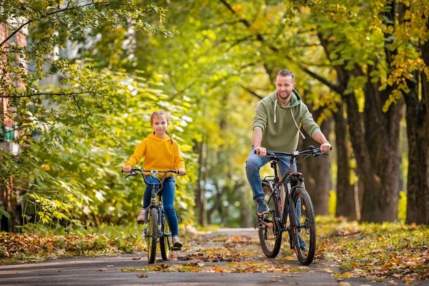Szczęśliwy ojciec i córka jeździć na rowerach w jesiennym parku w słoneczny dzień.